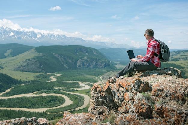 산에 앉아 노트북으로 야외에서 일하는 성인 남자. 원격 작업 또는 프리랜서 라이프 스타일의 개념.