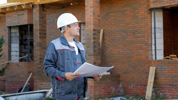 Adult man working on site of modern house and standing outdoors with paper draft looking away