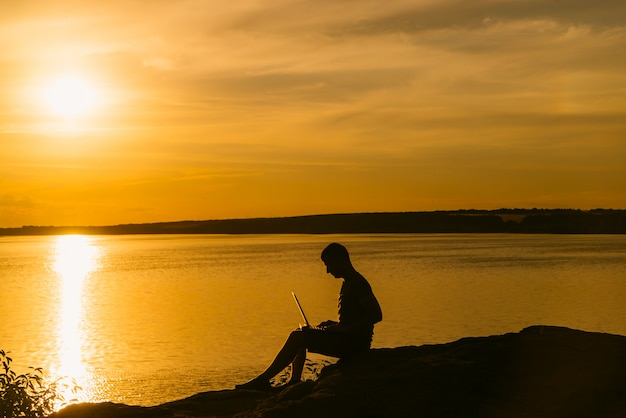 An adult man works at a laptop near the river