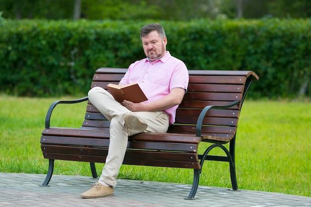公園のベンチに座ってフィクションを読んでいる大人の男性
