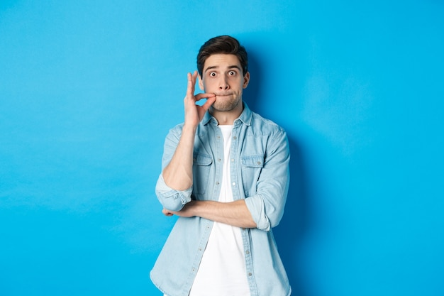 Adult man zipping mouth, promise keep secret, making a seal on lips and standing over blue background