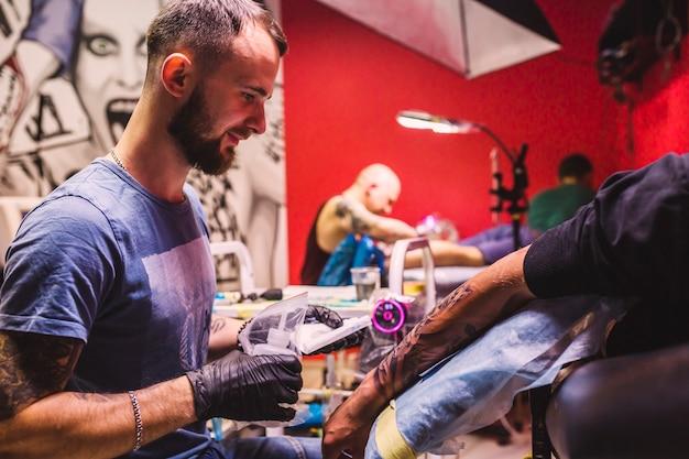 Взрослый мастер в студии татуировки