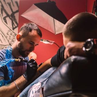 Взрослый мастер, делающий татуировку на руке