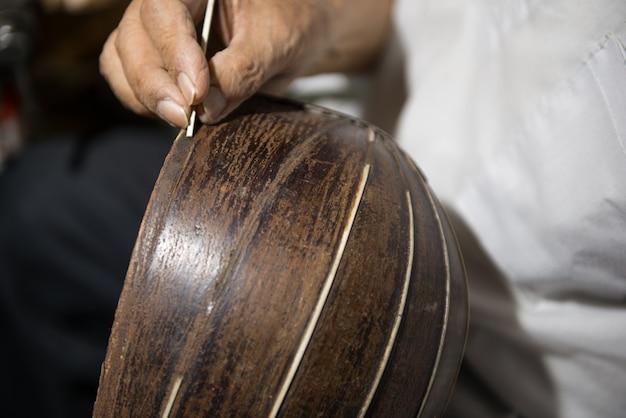 성인 마스터는 오래된 악기를 복원합니다. 나무 조각