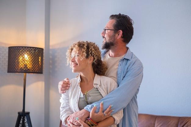 大人の成熟したカップルは愛とロマンスと抱き合って一緒に屋内でホームレジャー活動を楽しんでいます