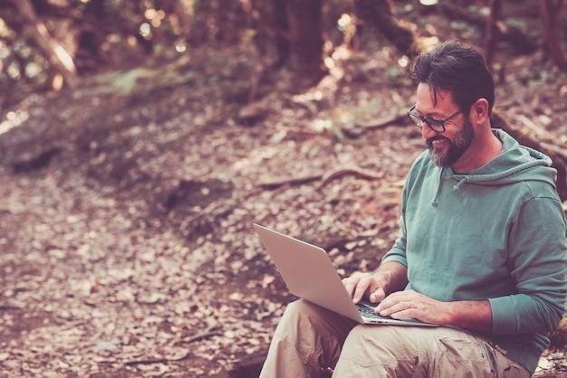 大人の成熟した男性は森の真ん中でローミングインターネット接続を備えたラップトップコンピューターを使用します-リモートワーカーとスマートに働く現代人の概念-ハンサムな男性はワイヤレスの新しい仕事を楽しんでいます