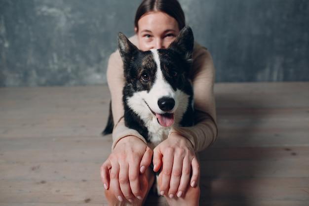 Corgi 개 애완 동물과 함께 거실에서 집에서 요가 하 고 성인 성숙한 여자