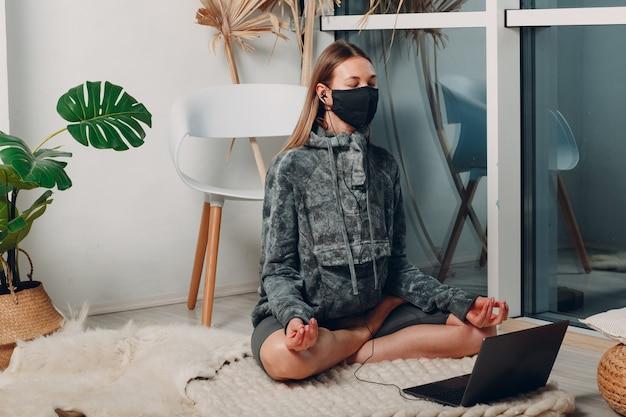 ノートパソコンのオンラインチュートリアルで自宅のリビングルームでヨガをしている大人の成熟した女性