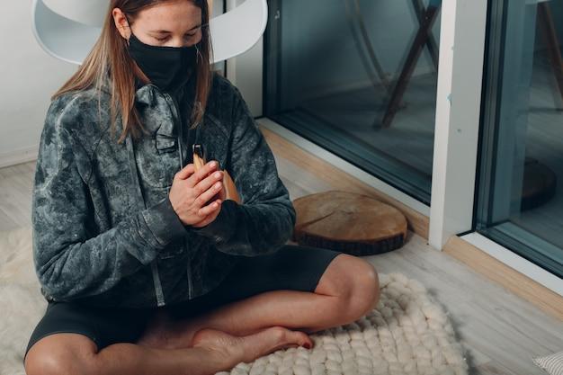 パロサントスティックツリー香を吸って自宅のリビングルームでフェイスマスクでヨガをしている大人の成熟した女性