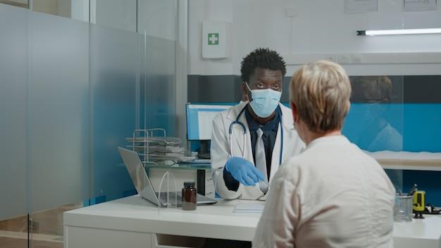 コロナウイルスに対するガラスの保護を備えた机に座っている高齢の患者と治療について話し合う成人の薬。年次健康診断の予約時にフェイスマスクを持った医師と老婆