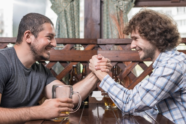 Adult men arm wrestling in pub