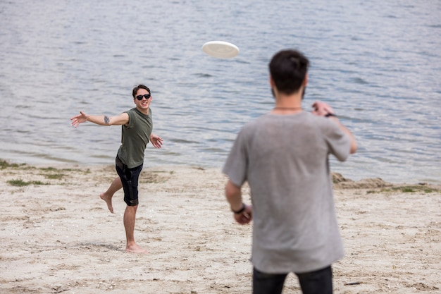 Adult men playing frisbee on shore during holidays