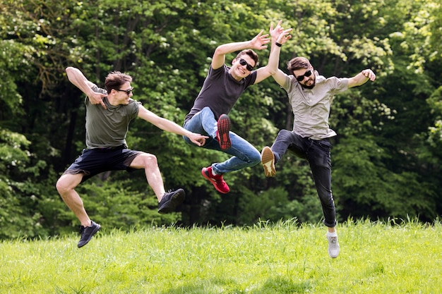 Adult men posing and jumping in mid air