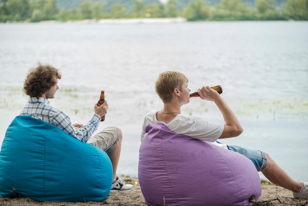 Adult men relaxing with beer near water
