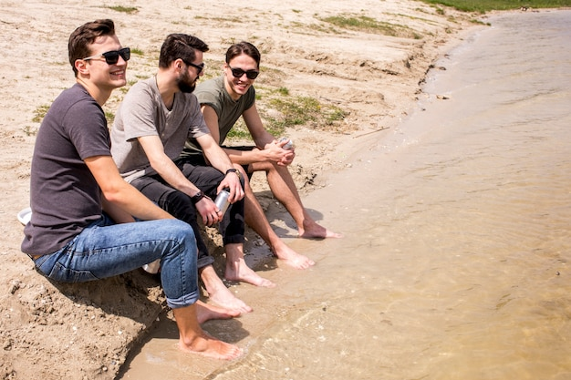 Adult men sitting on beach with legs in water