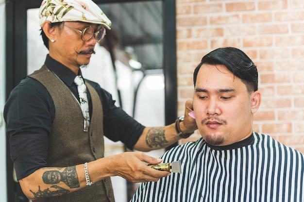 Взрослый мужчина стильный парикмахер с татуировками и стрижкой усов клиента в парикмахерской