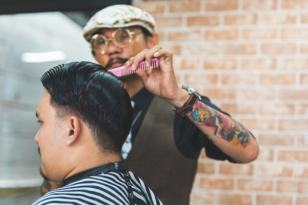 Adult men stylish hairstylist with tattoos and mustache cutting hair of customer in barber shop