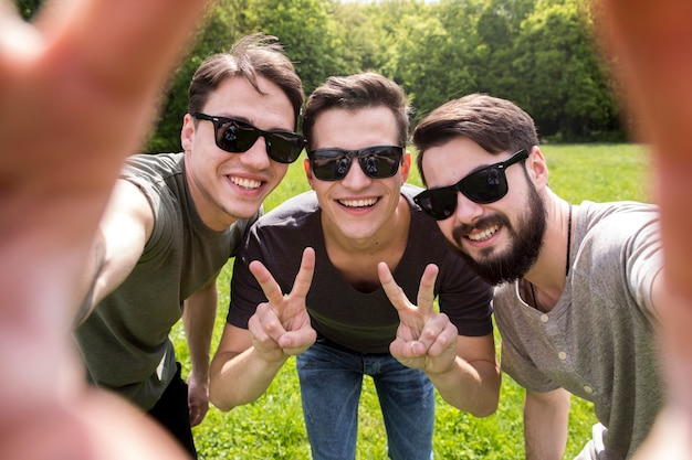 Adult men in sunglasses taking photo on smartphone