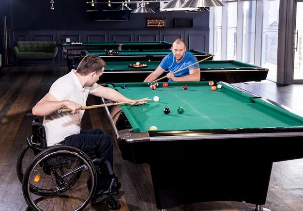 車椅子の障害を持つ成人男性は、クラブでビリヤードをします
