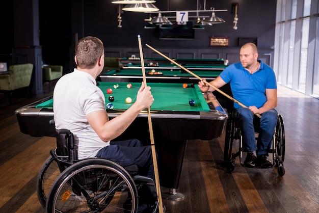 Взрослые мужчины с ограниченными возможностями в инвалидной коляске играют в бильярд в клубе