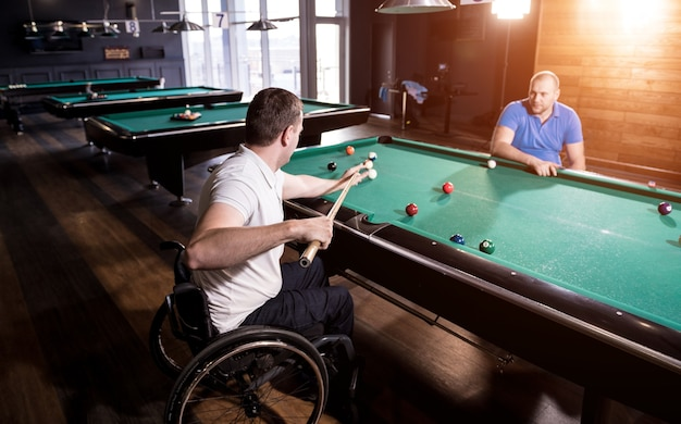 Adult men with disabilities in a wheelchair play billiards in the club