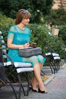 Adult middle-aged business woman sitting on a park bench and makes notes in a notebook, checking with a smartphone