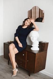 빈티지 인테리어에 가까운 눈을 가진 포즈 어두운 파란색 드레스에 성인 모델 여자.