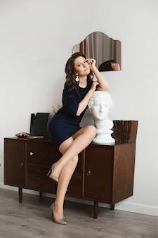 빈티지 인테리어에 동상 머리와 함께 포즈를 취하는 짧은 진한 파란색 드레스에 섹시 한 다리를 가진 성인 모델 여자.