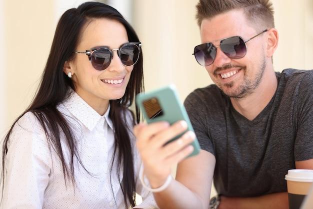 Взрослые современные модные люди смотрят на портрет экрана смартфона.