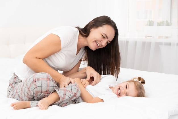 大人の母親は、自宅のベッドで小さなアクティブな娘をくすぐり、子供たちとの余暇活動をしています。