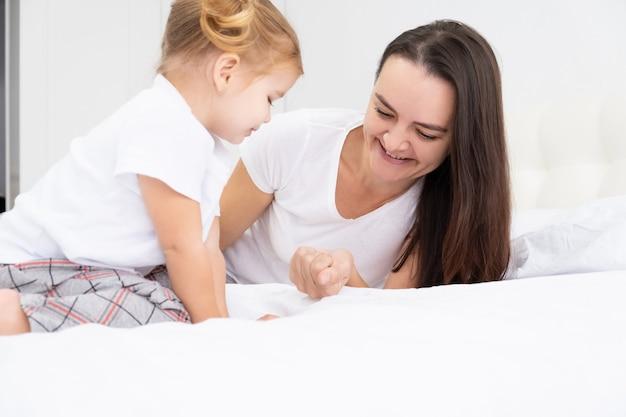 大人の母親は家で小さなアクティブな娘と遊んで、子供たちと一緒に楽しい余暇活動をしています。