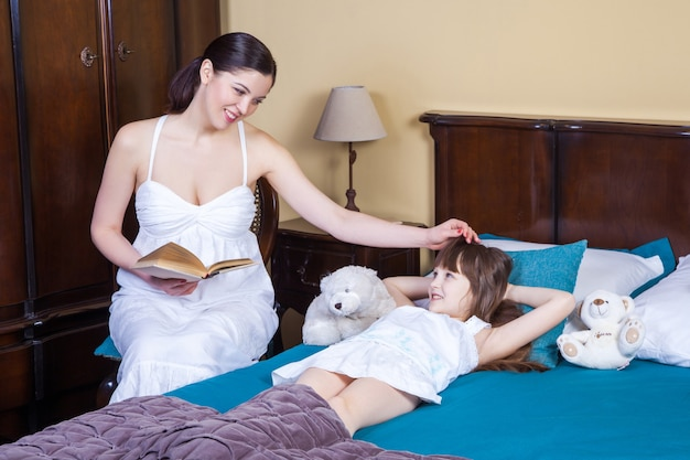 Adult mother teaches her daughter to read touching her head