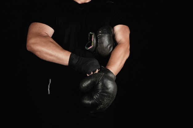 Adult muscular man in black clothes puts on leather black boxing gloves