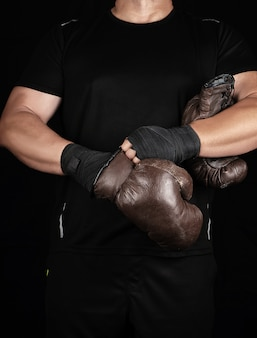 Adult muscular man in black clothes puts on leather brown boxing gloves on his hands