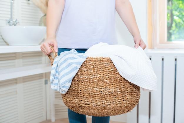 大人の老婦人は、短い黒髪で家事をします。きれいな服を籐の洗濯かごに入れて笑顔。