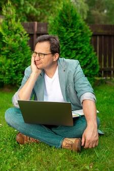 ノートパソコンとノートブックを持って芝生に座っているビジネスカジュアルの大人の物思いにふける男性の創造的な労働者は目をそらし、男性の著者は本、自伝に取り組んでいます。フリーランサーの作品、ジャーナリズムのリモートワークのコンセプト