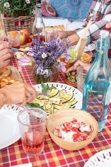 大人が一緒に食事を楽しむ手がテーブルの上で何かを取る