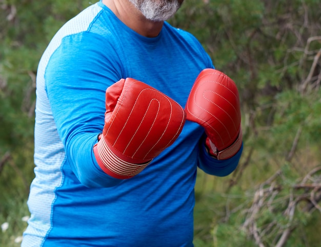 Adult plump athlete in blue uniform and red leather boxing gloves