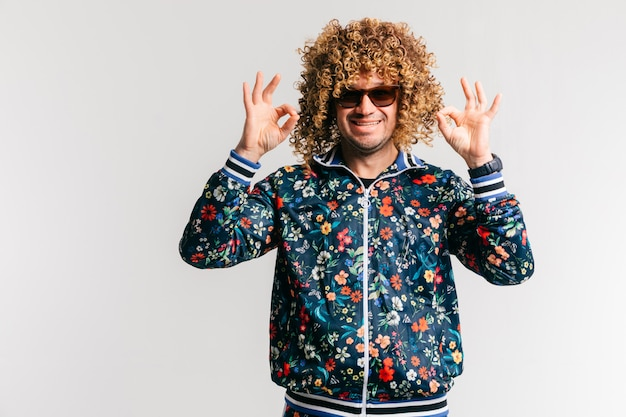 Adult positive smiling funky man in flowered jacket showing ok gesture over white background.