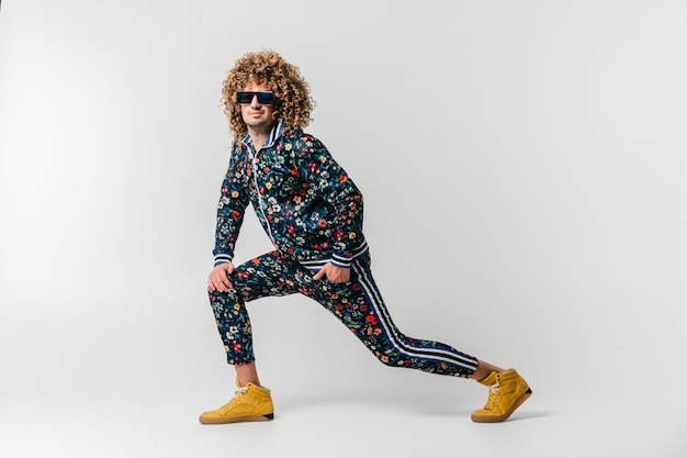 Adult positive smiling funky man with curly hair style in suglasses and vintage clothes posing