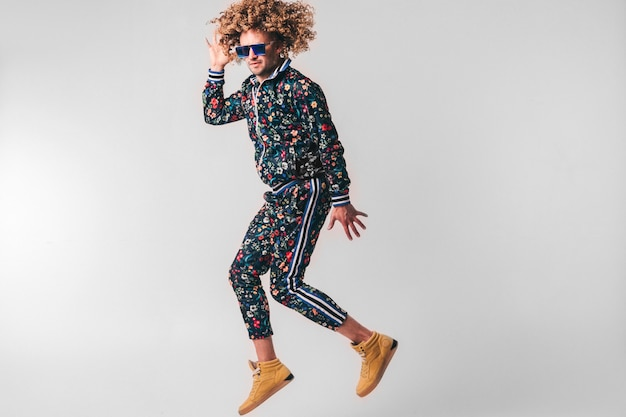 Adult positive smiling funky man with curly hair style in sunglasses and vintage clothes posing on white wall. funny portrait of stylish male person.