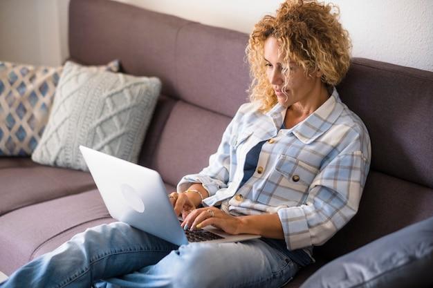 大人のきれいな女性の人々は、インターネットコンピュータのコンテンツが自宅のソファに横になってリラックスしているのを見る-女性の笑顔がディスプレイを見て、代替の仕事と仕事のライフスタイルを楽しむ-眼鏡をかけた女性