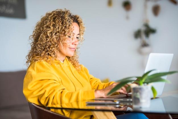 現代のスマートなウォーキングと仕事の代替オフィスブロンドの巻き毛とテクノロジーインターネット接続の美しい人々のテーブルコンセプトでラップトップコンピューターを使って自宅で働く大人のきれいな女性