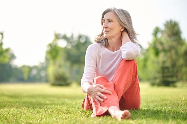 Взрослая красивая женщина медитирует на лужайке в парке