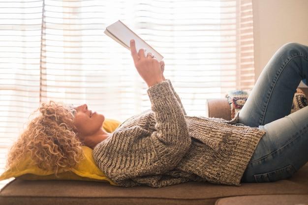 Взрослые расслабленные красивые вьющиеся светлые волосы кавказской женщины легли и читали бумажную книгу в одиночестве дома с оконным светом