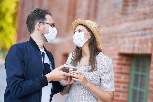 街の散歩でマスクを身に着けている大人のロマンチックなカップル