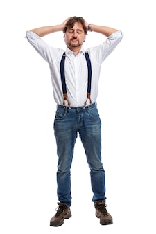 An adult sad man in jeans and a white shirt stands and holds his head. pain, stress and depression. full height. isolated on white background. vertical.