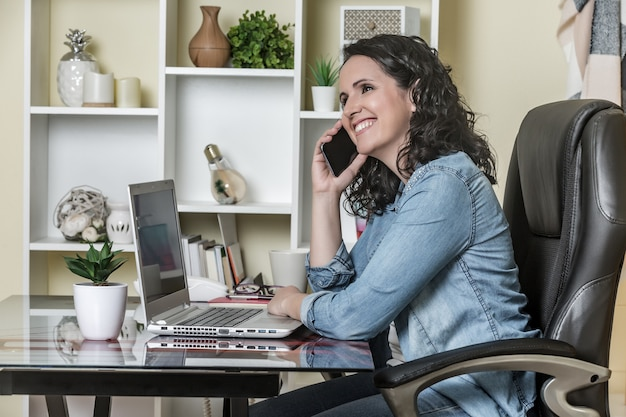 Adult satisfied businesswoman making phone call while working on laptop in light contemporary office