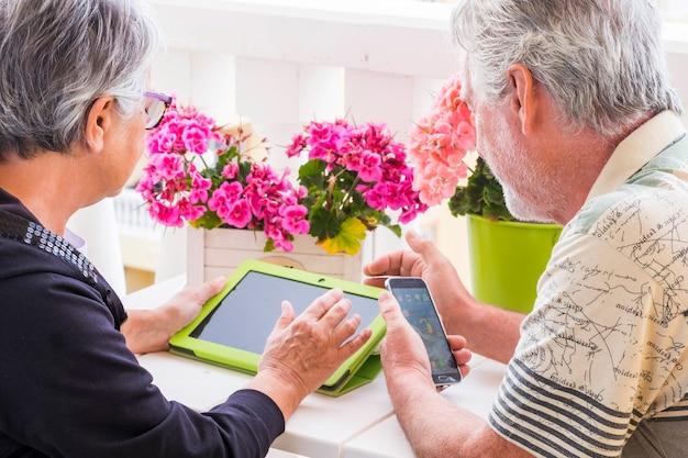 성인 수석 부부는 집에서 테라스에서 노트북 야외 레저 활동을 사용합니다. 일없이 하루 종일 함께있는 좋은 날씨와 은퇴 한 삶을 웃으며 즐기십시오. 기술을 사용하여 머무르다