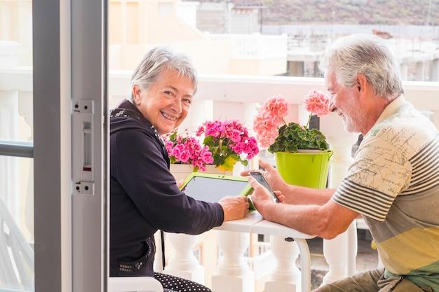 大人の年配のカップルは、自宅のテラスでラップトップの屋外レジャー活動を使用します。笑顔で天気の良い日を楽しみ、仕事をせずに一日中一緒に暮らす引退生活を楽しんでください。テクノロジーを使って滞在する